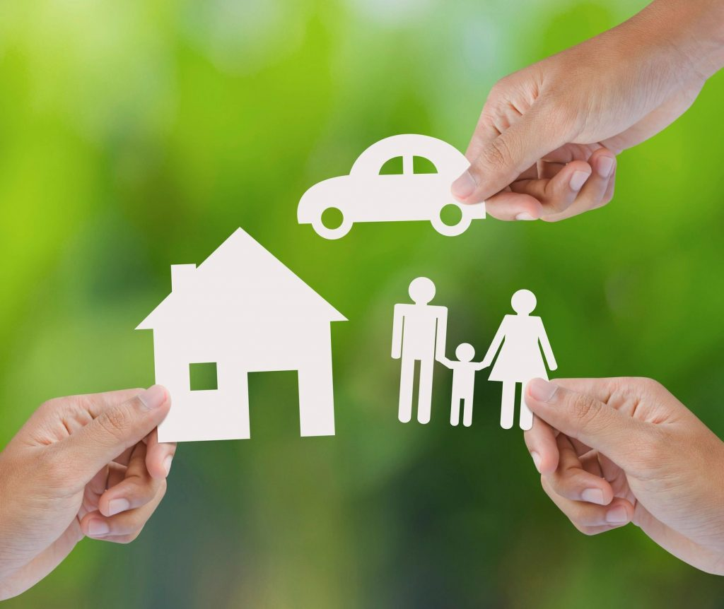 Three hands holding white cut-outs of an icon of a car, house, and a family