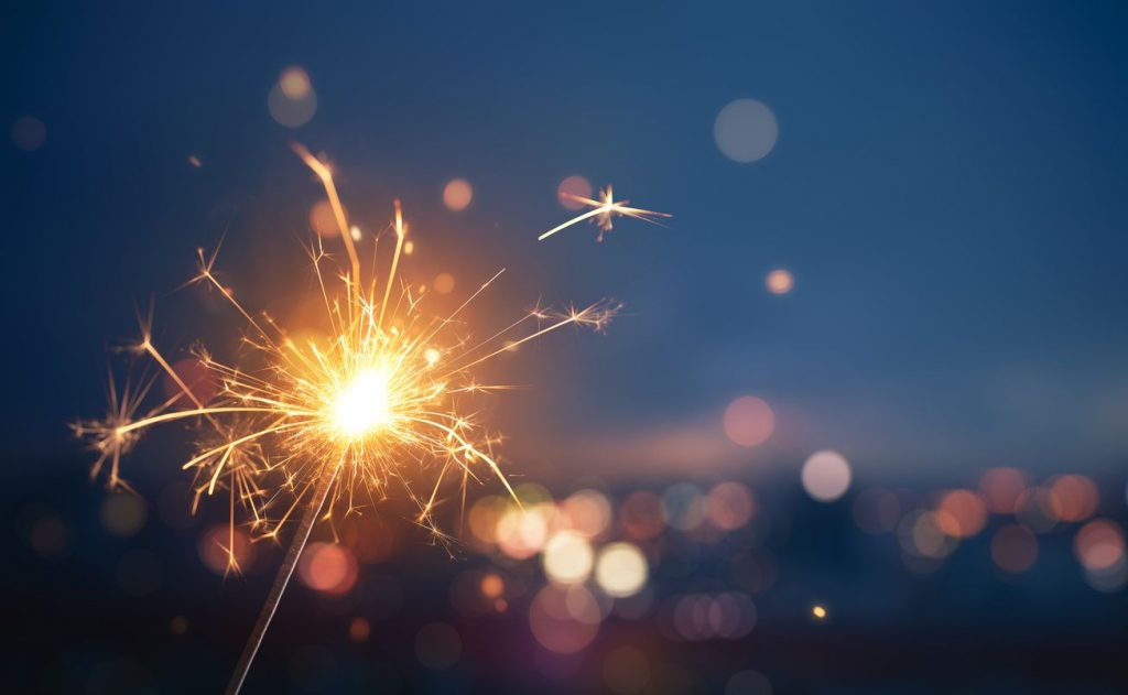 Close-up of a sparkler with out-of-focus city lights in the background