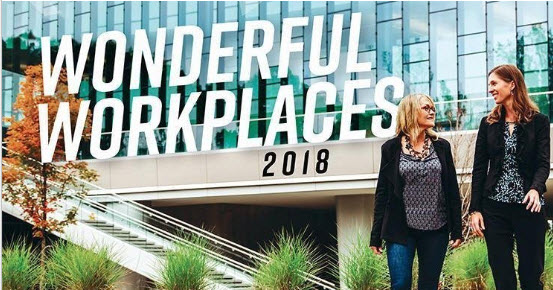 Two women outside of an office building with a glass facade and a Wonderful Workplaces 2018 logo