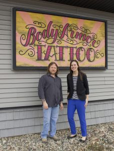 A man and a woman standing in front of a Body Armor Tattoo sign