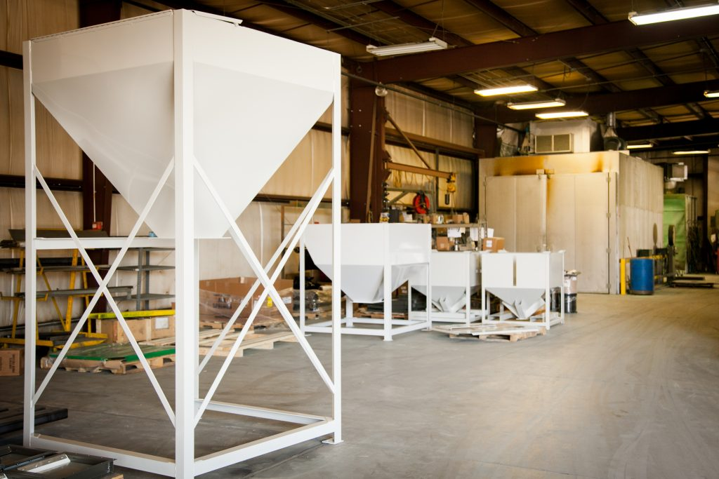 A fabrication workshop with four white industrial funnels