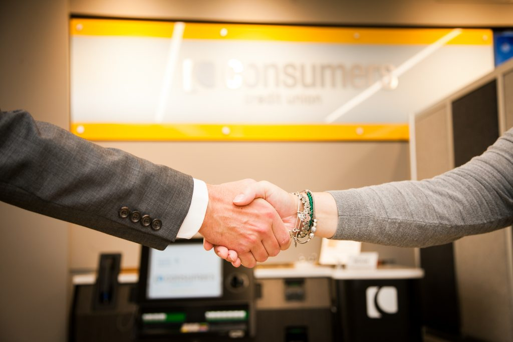 A man and a woman shaking hands in front of a Consumers Credit Union sign on an office wall