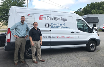 Two men posing for a shot outside of a Grand Office Supply delivery van