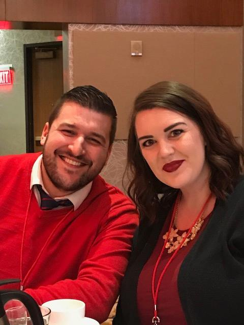 A man and woman sitting at a dinner table wearing red and smiling