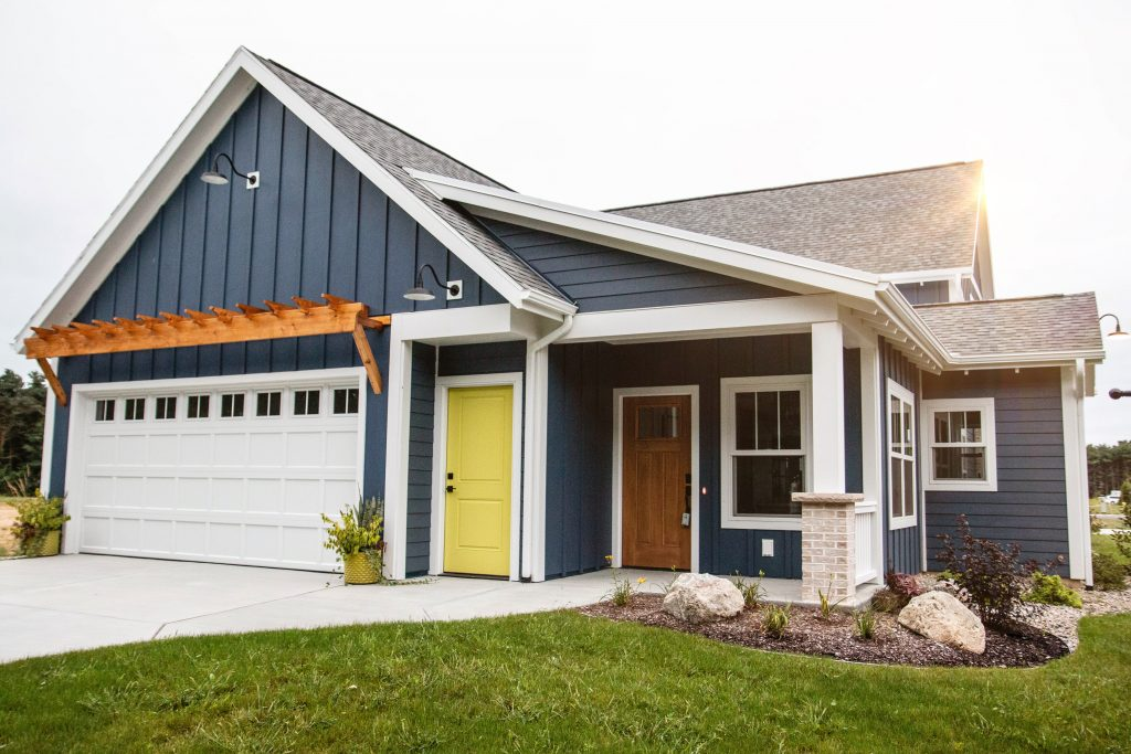 Blue house with white trim, grey roof, and yellow door