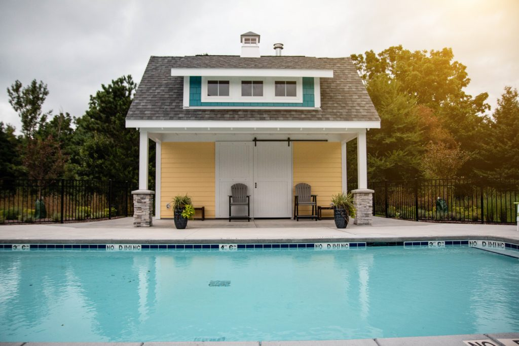 A yellow and modern pool shed in front of a pool