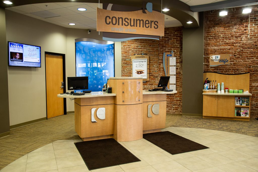 A customer service stations with silver Consumers Credit Union logos
