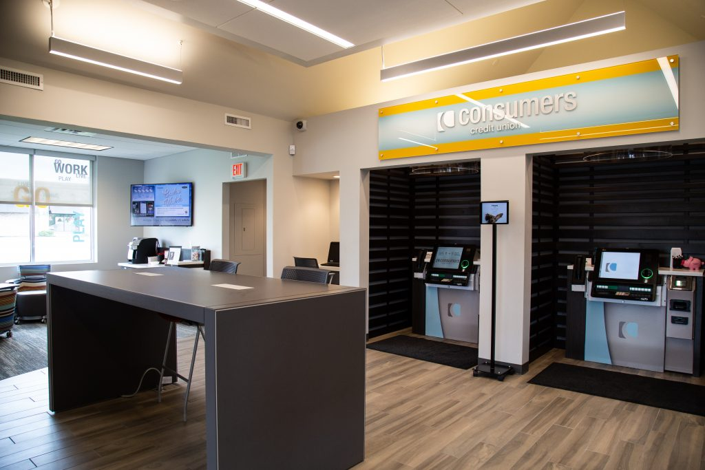 A Consumers Credit Union office with with two personal ATM kiosks and a standing height table in the middle of the room