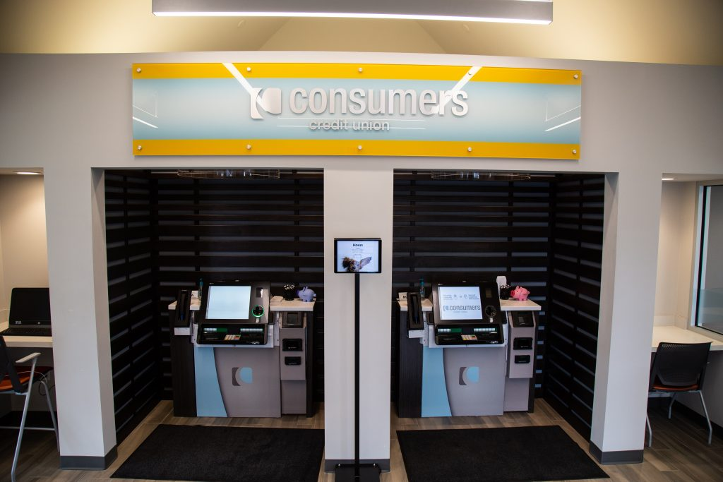 Two ATM kiosks underneath a yellow Consumers Credit Union sign