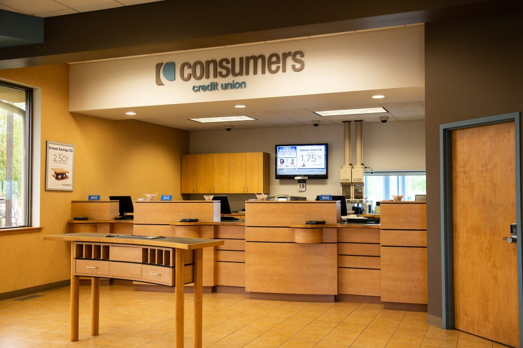 A Consumers Credit Union office front desk with three bank teller windows and a curved bank slip kiosk