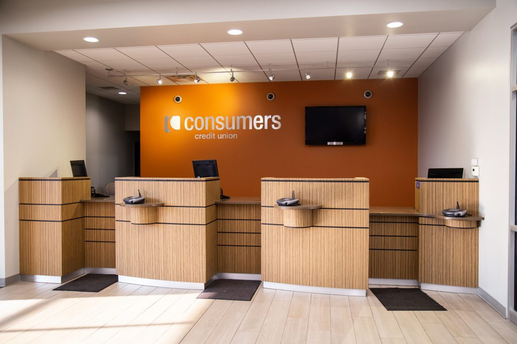 A Consumers Credit Union bank teller windows with an orange wall in the background