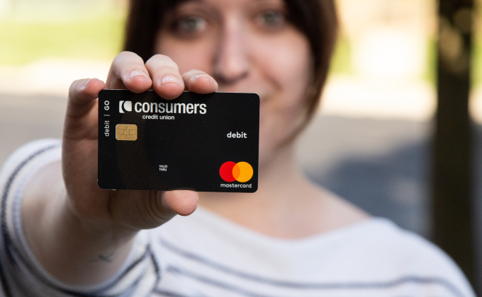 A woman holding a black Mastercard Consumers Credit Union debit card