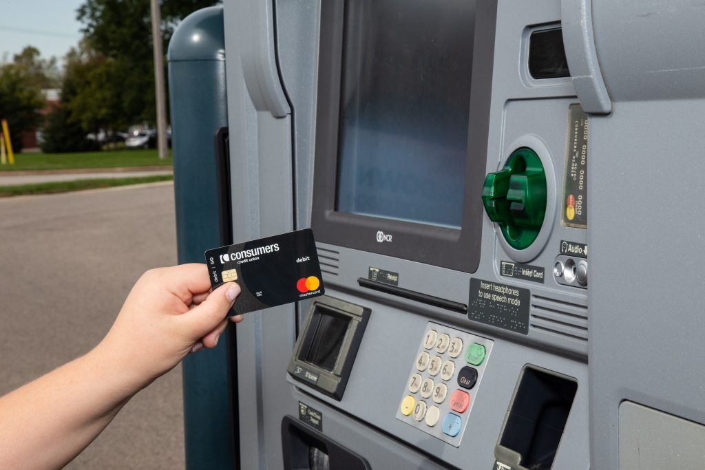 A black Mastercard debit card from Consumers Credit Union being inserted into an ATM