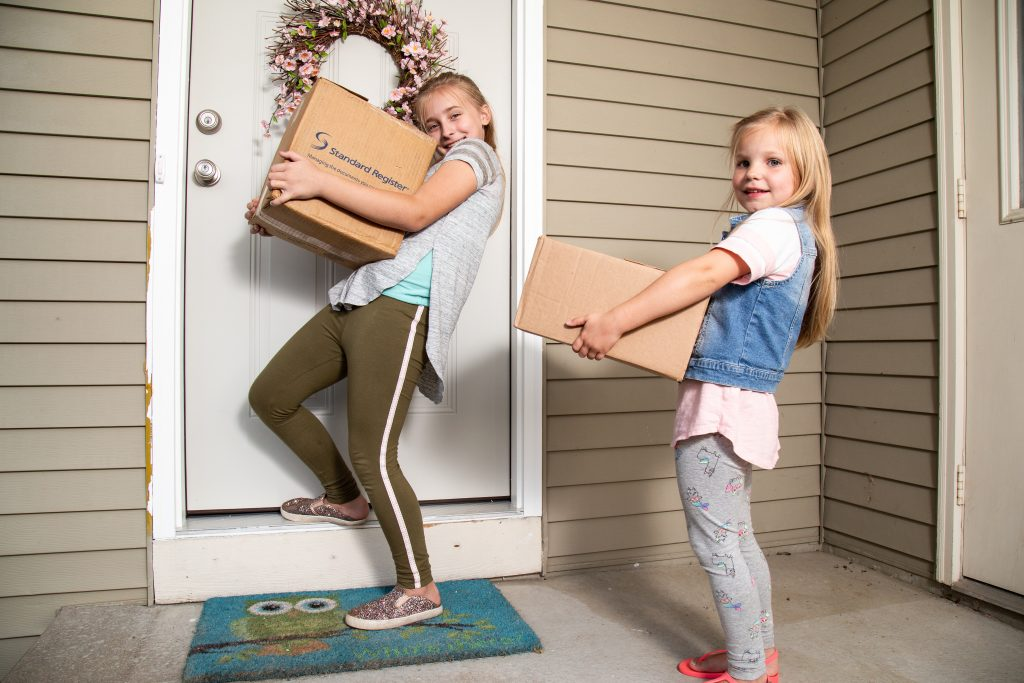 Two young girls holding cardboard boxes on a front porch about to enter the door