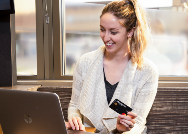 A young woman holding a black Mastercard Consumers Credit Union debit card making an online purchase