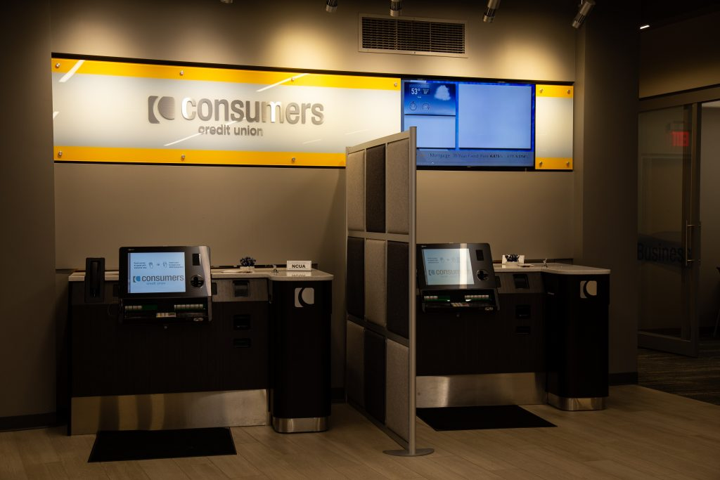 Two personal banking kiosks under a yellow Consumers Credit Union signs