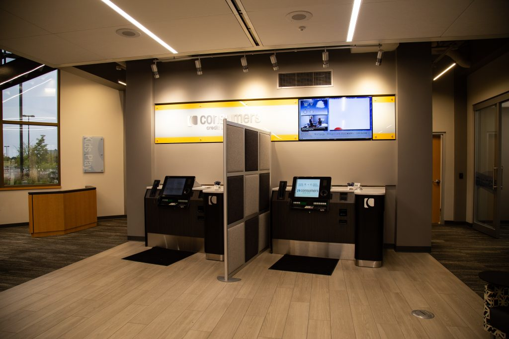Two banking kiosk separated by a grey and black checkerboard partition