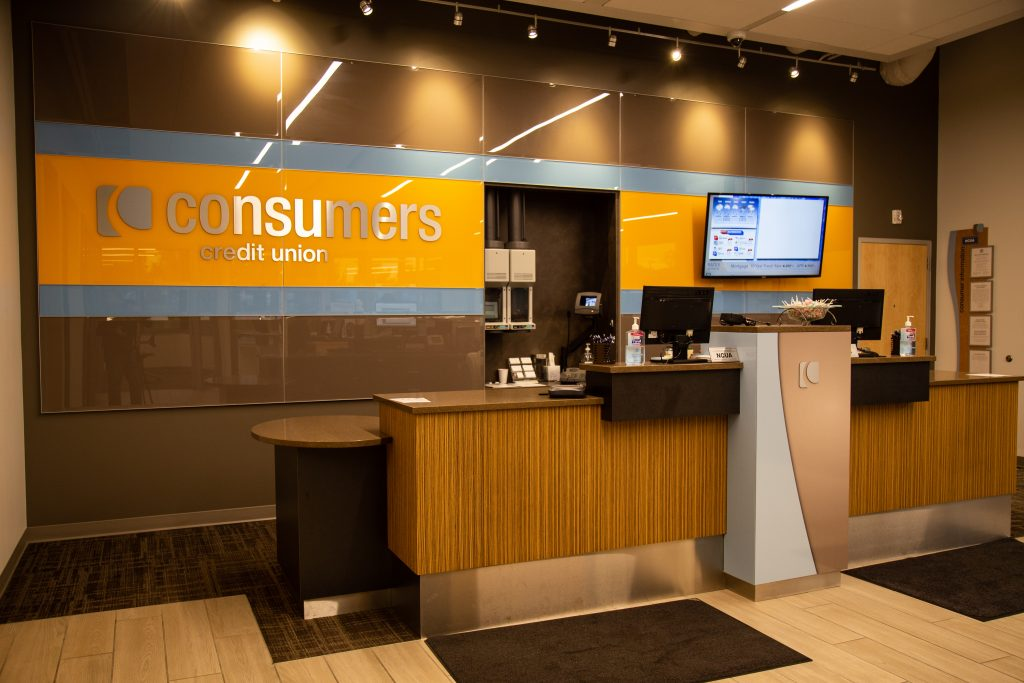 A Consumers Credit Union office with dark wood finish and an orange Consumers sign on a brown wall
