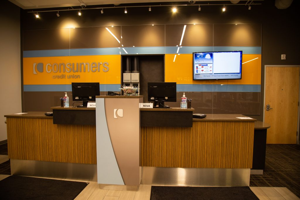 A Consumers Credit Union office with an orange Consumers sign behind two teller desks