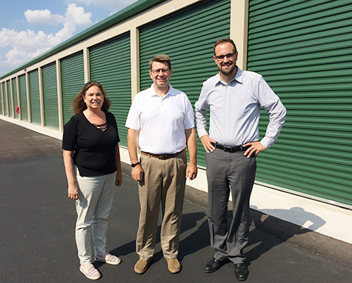 Two men and a woman standing outside of storage unit facility with green doors on a sunny day