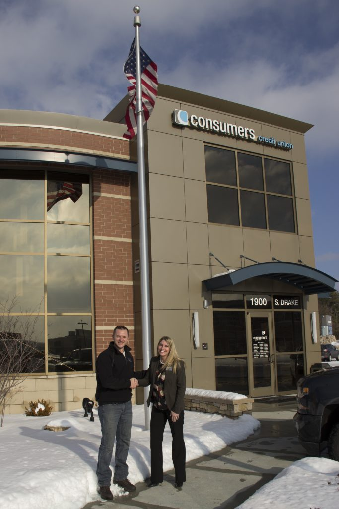 A young man and woman shaking hands outside of a Consumers Credit Union office on a snowy day