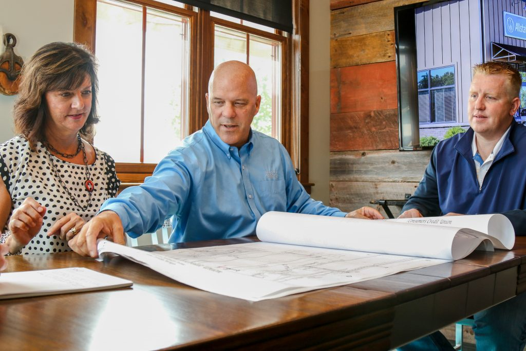 Two men and a woman sitting at a table with blueprints spread out on a table