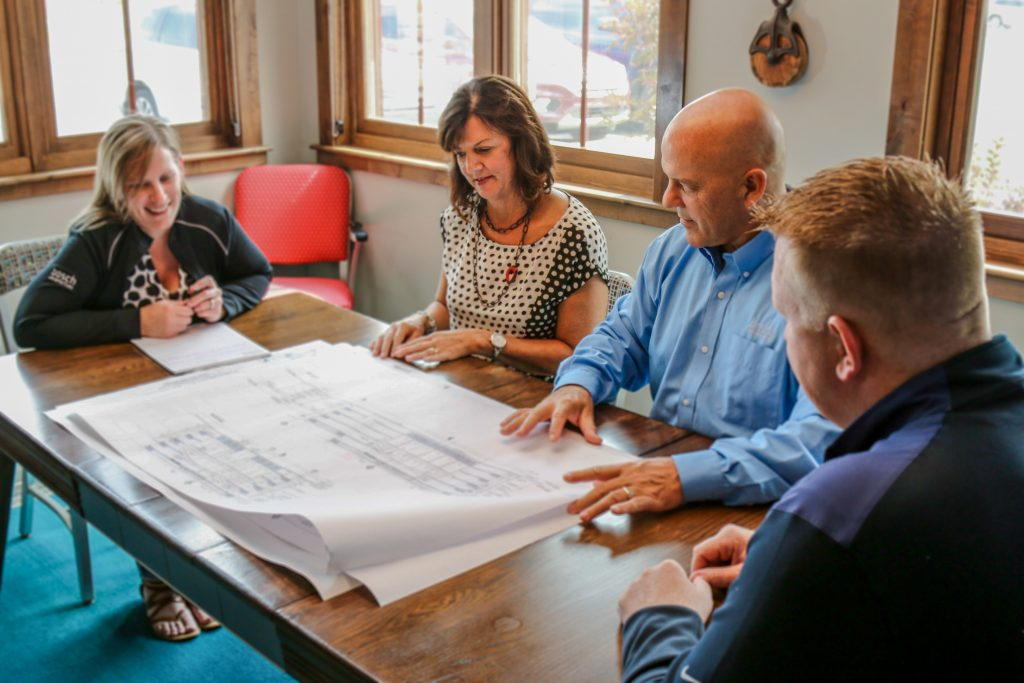 Four people looking at blueprints at a table