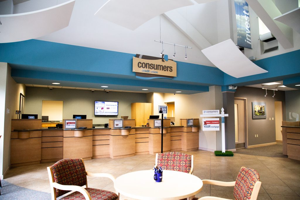 A round table with three chairs in front of four Consumers Credit Union teller windows