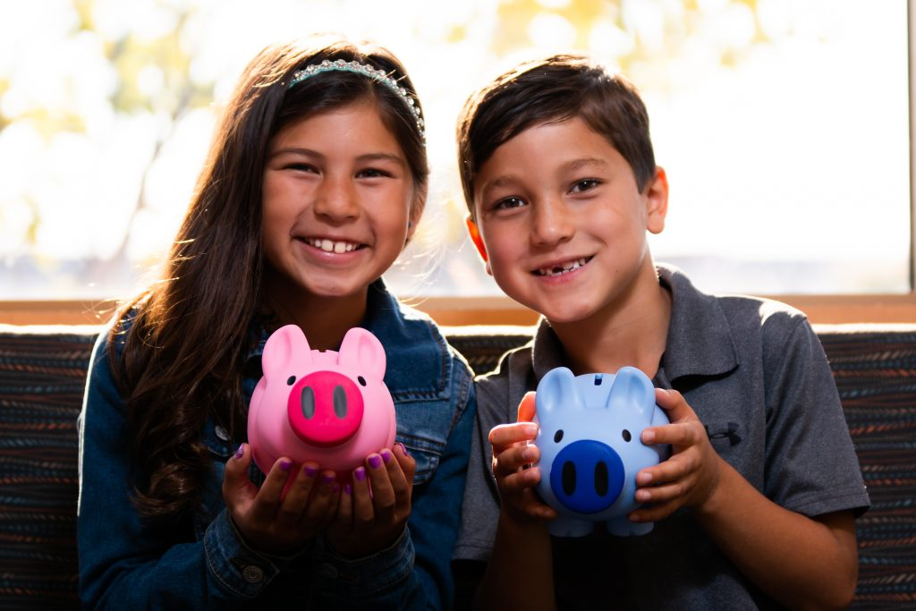 A young boy and girl smiling and holding piggy banks