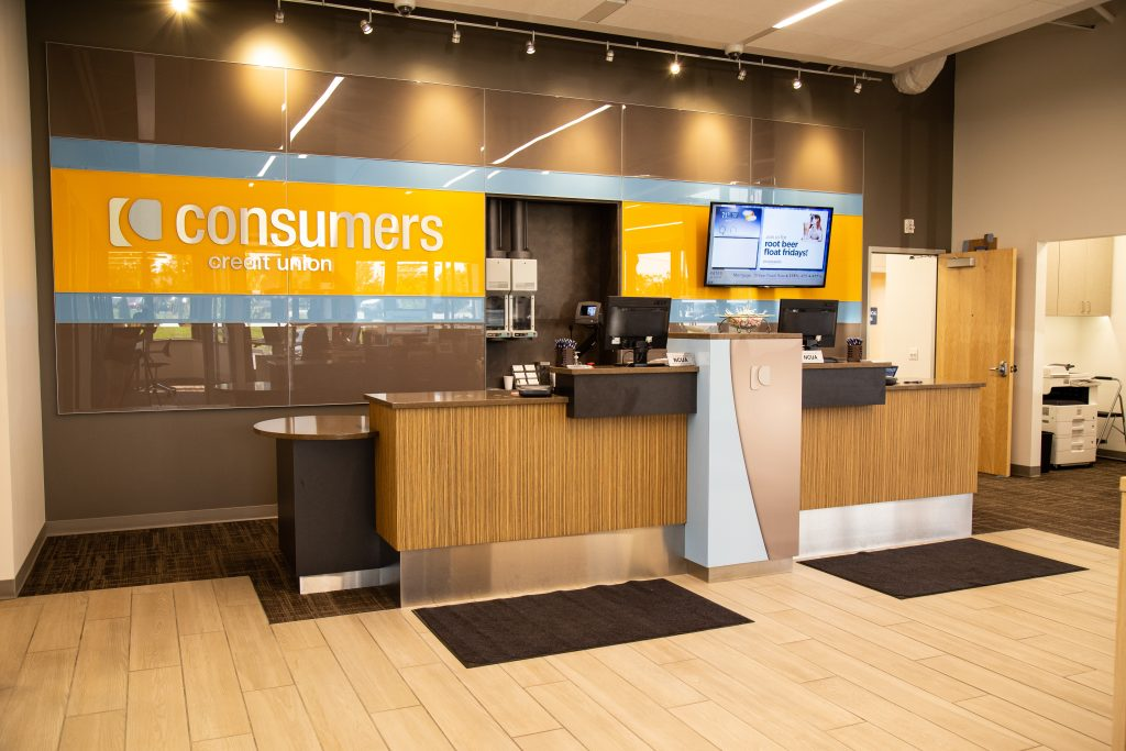 A Consumers Credit Union office with an orange Consumers sign behind the teller counter
