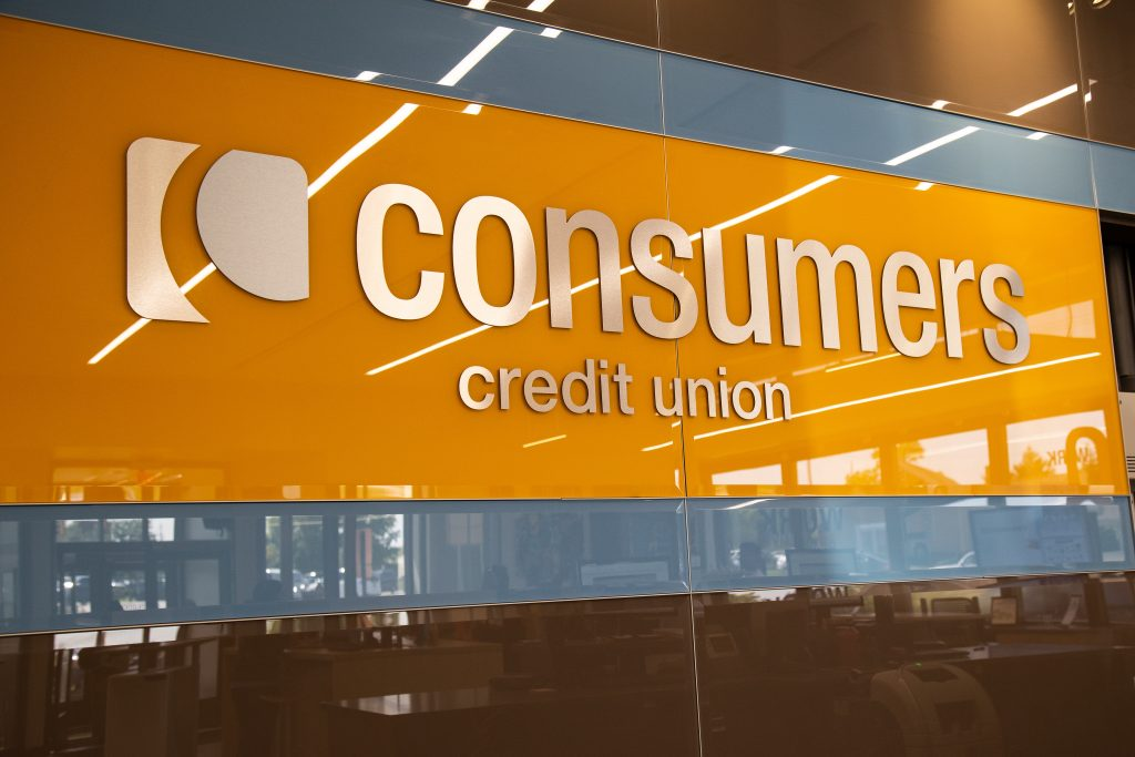 A close-up of an orange Consumers Credit Union sign