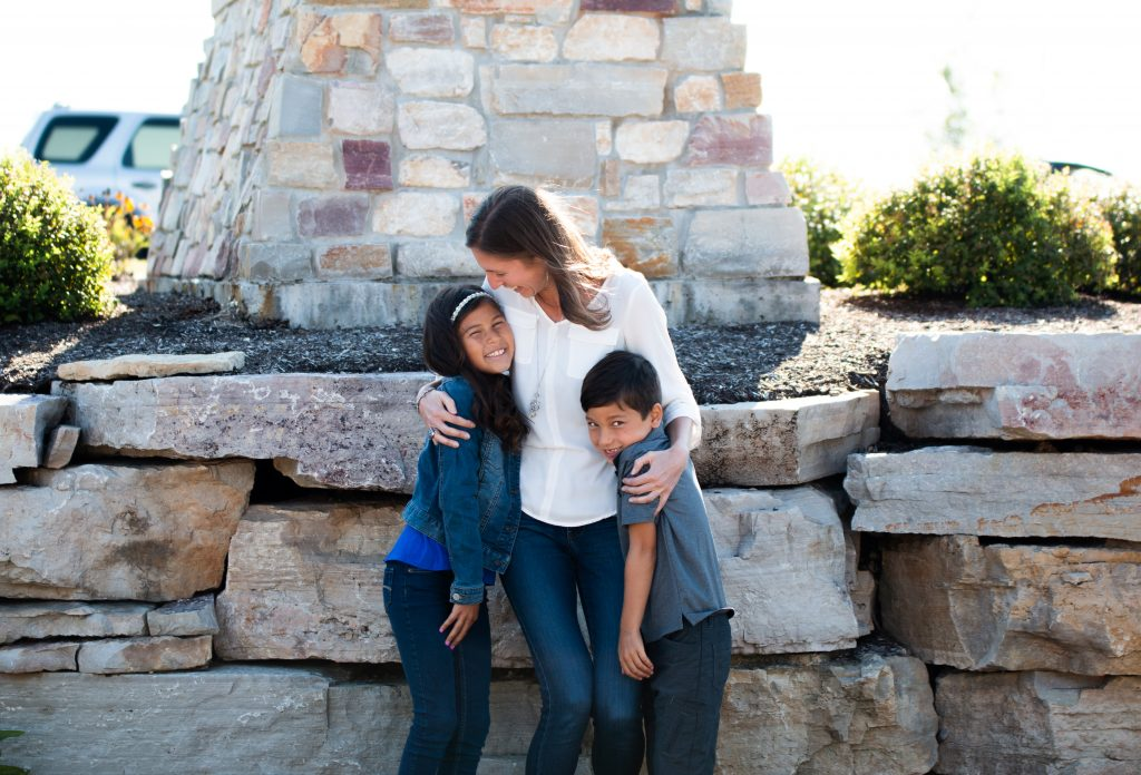 A woman embracing a boy and a girl in front of large stones and a brick structure