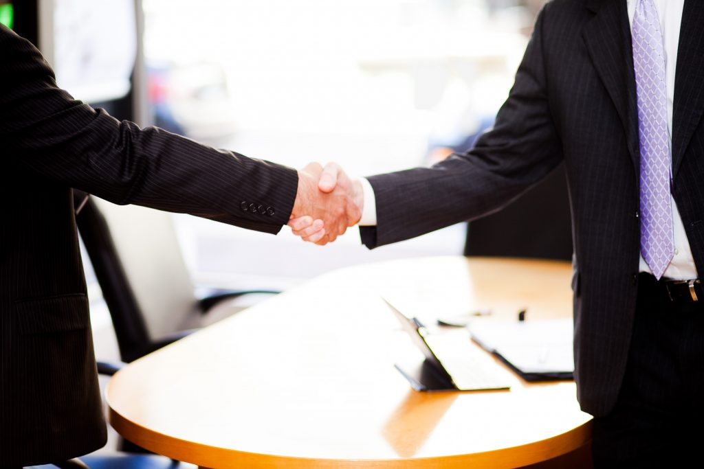 Two men standing and shaking hands in front of a table