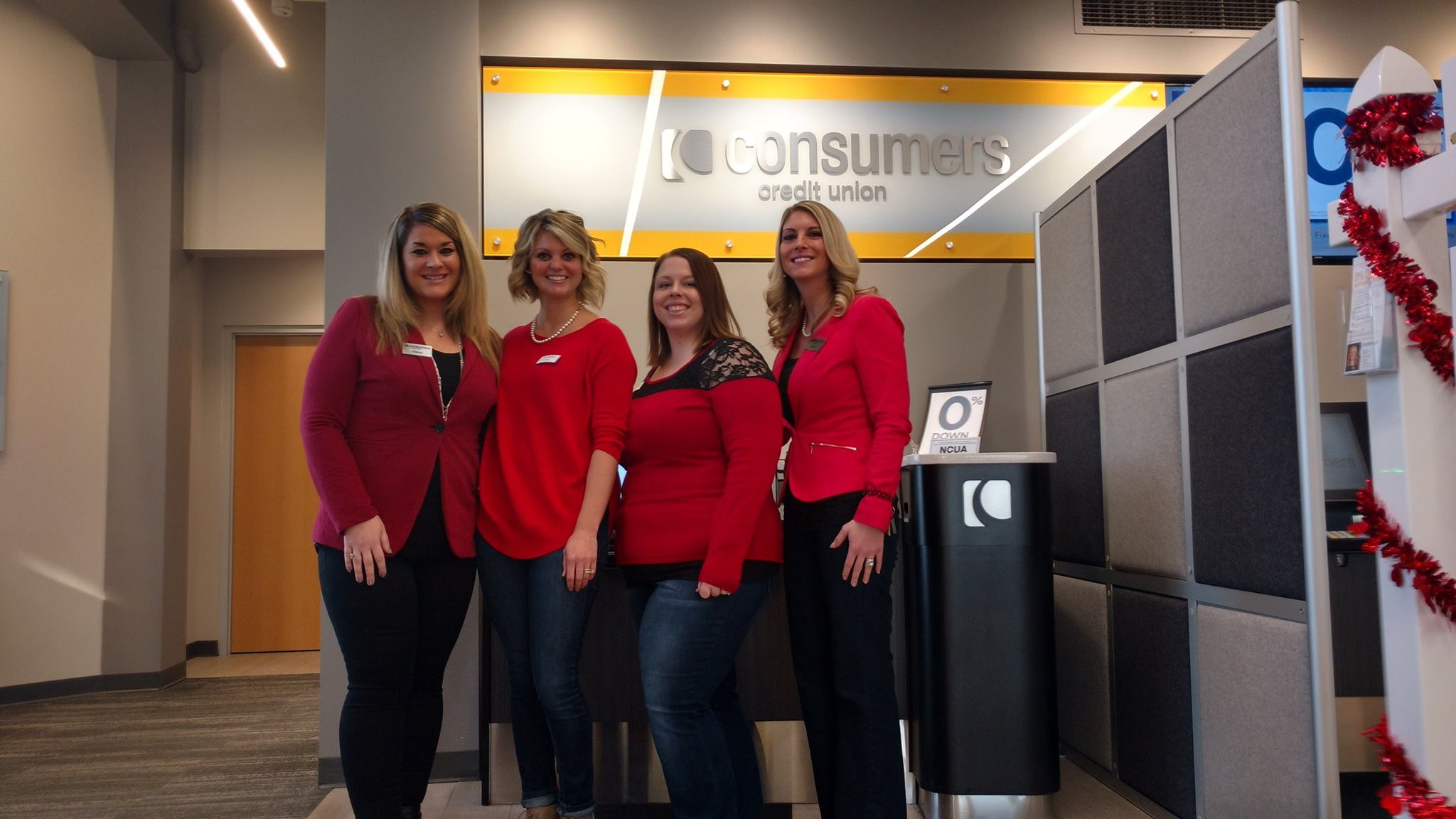 Four women in red smiling in front of an orange Consumers Credit Union sign
