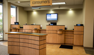 A Consumers Credit Union office with teller service counter in the background and a standing height kiosk for withdrawal and deposit slips in the foreground