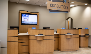 A Consumers Credit Union branch with three teller stations and a TV screen behind them