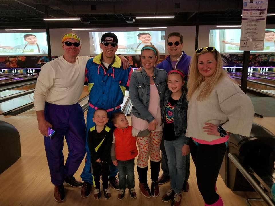 A group of people happily posing in front of bowling alley lanes