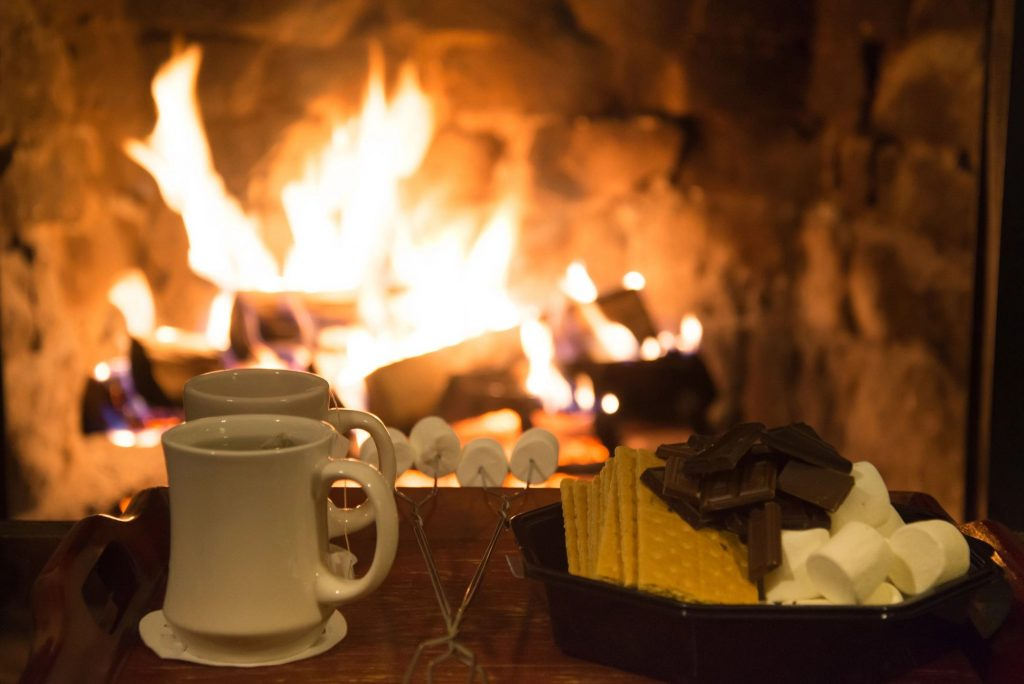 A two cups of tea, roasting sticks with marshmallows, and ingredients for s'mores in front of a fire
