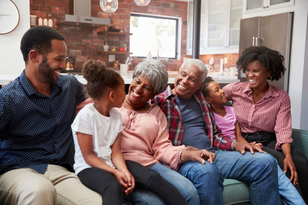 A pair of grandparents with their grandkids and the children's parents on a couch smiling