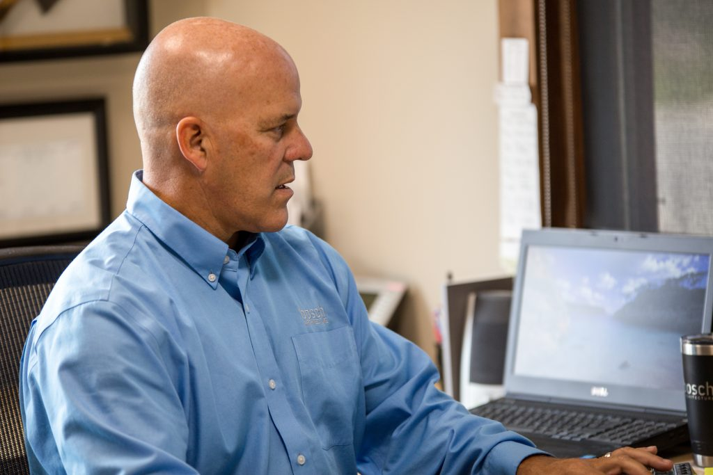 A man with a blue shirt working on a computer at a desk