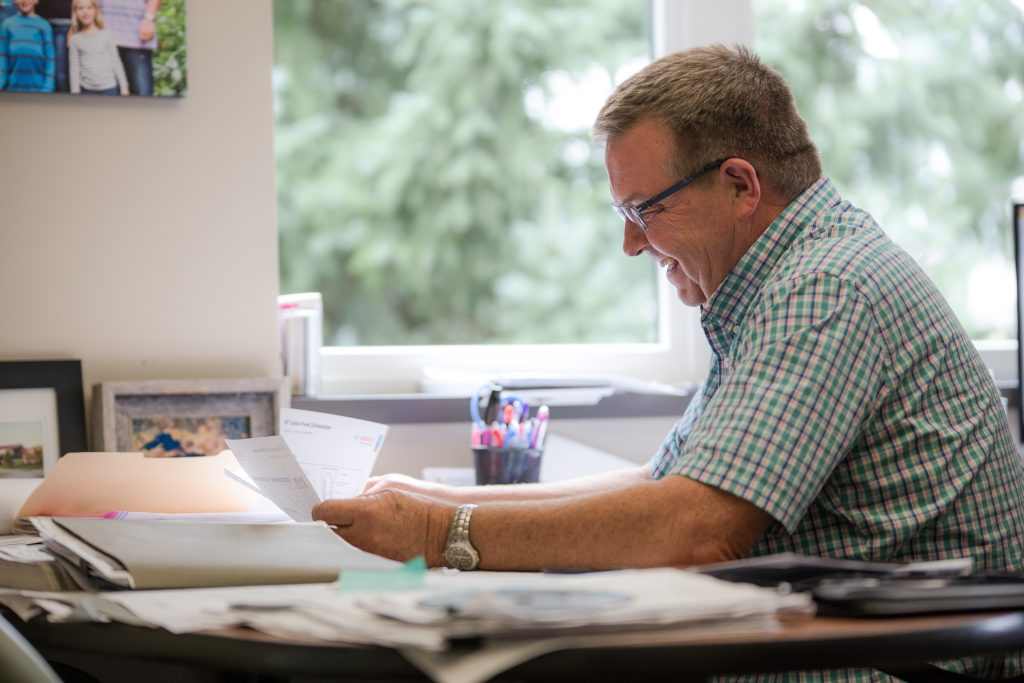 Man with glasses and a green plaid shirt sifting through paperwork on a desk