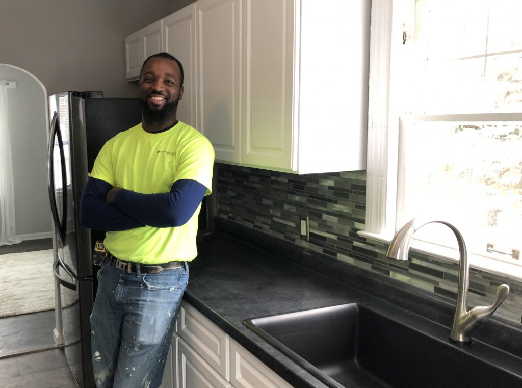 A carpenter leaning against a countertop in a kitchen smiling