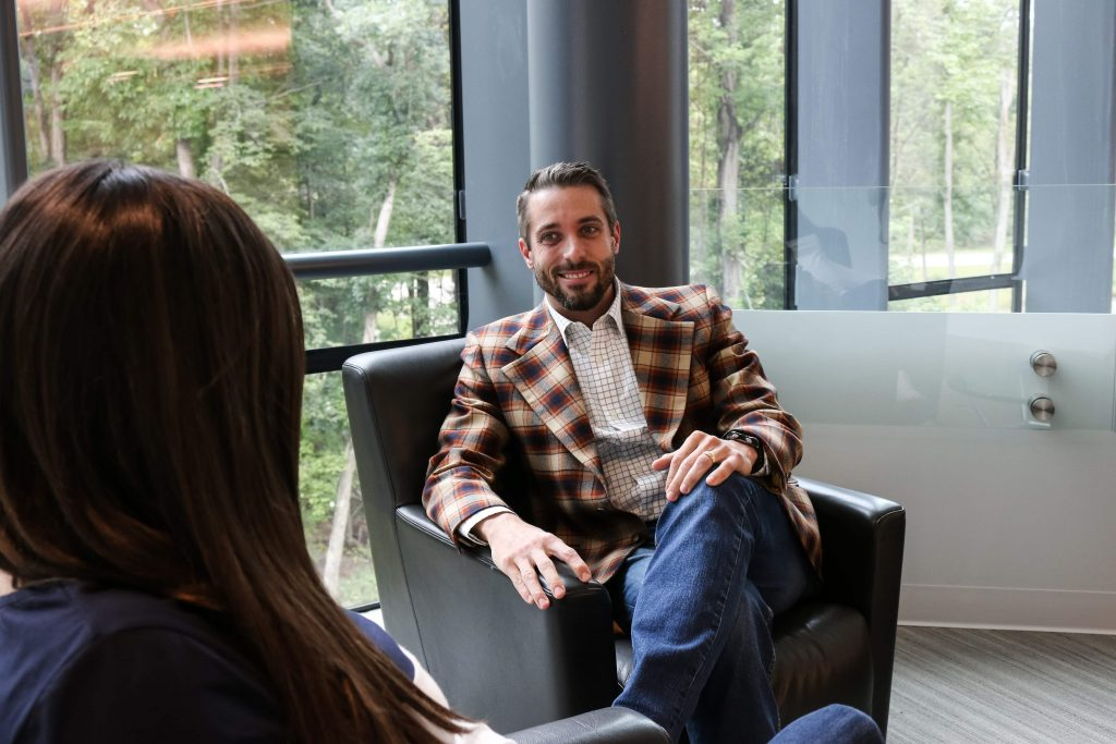 A bearded man with jeans and a plaid sport jacket in a lounge area