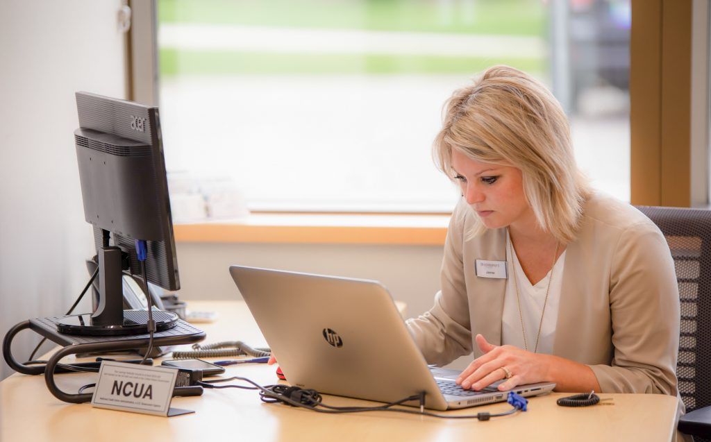 Blonde woman typing on a laptop in an office