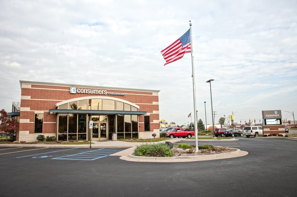 A Consumers Credit Union and a parking lot with an American Flag on a pole