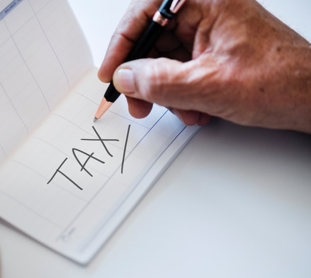 man writing the word tax