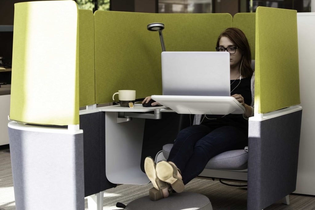 A woman working in a personal lounge cubicle on a laptop