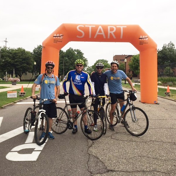 Four men on bikes standing in front of an orange Starting Point Arch