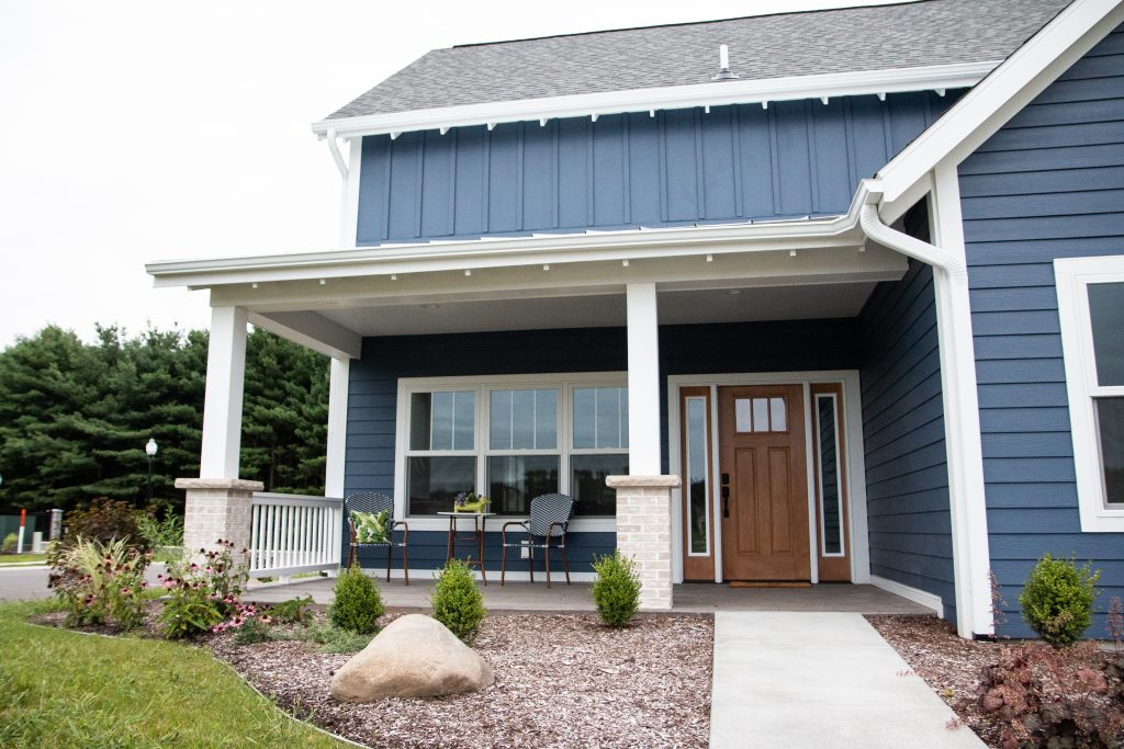 A large blue house with white trim and a large porch.