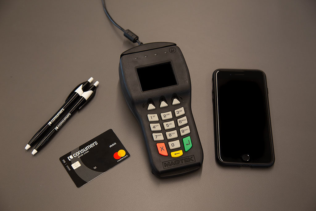 A credit card scanner with a black Consumers Credit Union debit card and two pens.